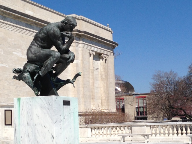 Rodin's The Thinker at front of Museum of Art with Peter B. Lewis Building shining in background.